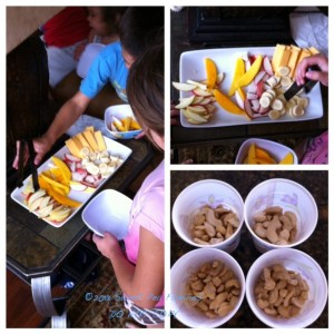 Sweet Pea Kiddos eating a healthy, whole food snack. Sliced fresh fruit, vegetarian cheese, and raw cashews