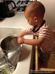 using the learning tower to help wash some dishes