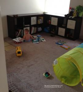 awake & enjoying his playroom, searching for the perfect read