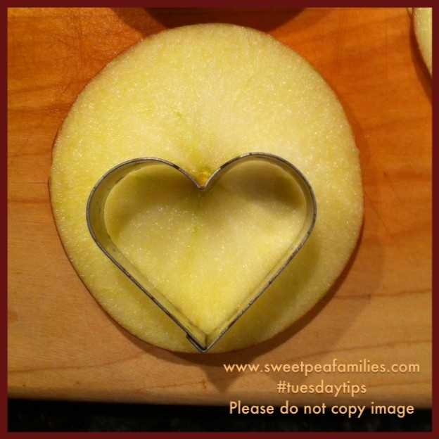 To get two hearts out of the same round, start by placing the wedge of the shape cutter over the stem of the apple.